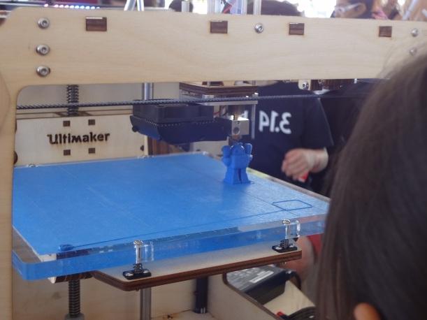 3-D printing machine making a robot figurine